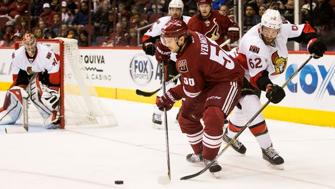 Coyotes center Antoine Vermette looks to pass as the Senators' Eric Gryba defends during the third period of the NHL game at Gila River Arena in Glendale on Jan. 10, 2015.