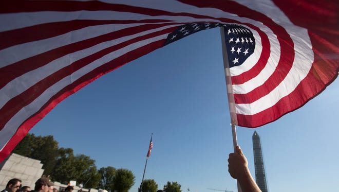Marine Terri Shreiner holds an American flag during a rally at the National World War II Memorial on Oct. 15 in Washington.