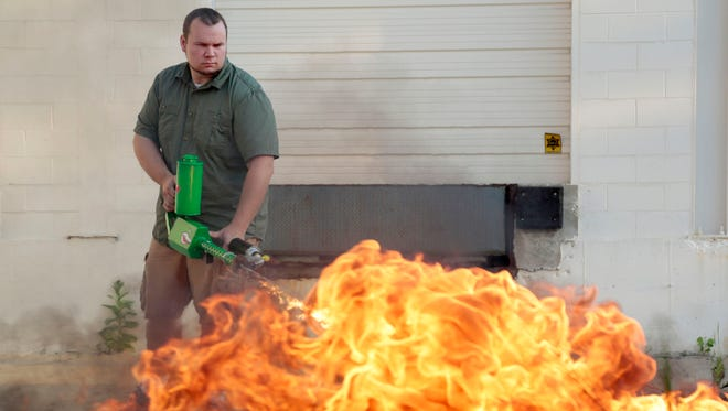 The Ion Productions Team Project Leader Chris Byars demonstrates the XM42 he dubs as the world first commercially available handheld flamethrower on Aug. 18, 2015.