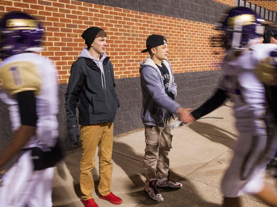 Waynesboro fans Taylor Norman, left, and Kevin Green, right, congratulate players as they walk off the field leading Hidden Valley during their Group 3A first round playoff football game on Friday, Nov. 14, 2014.