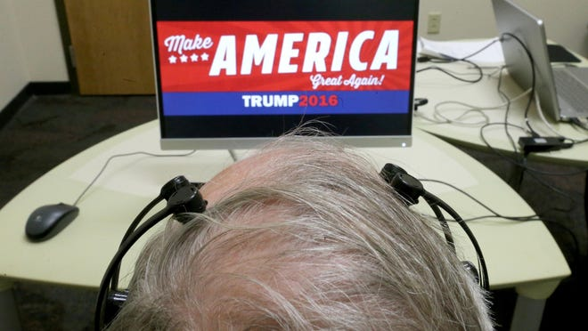 John MacWherter views a political advertisement for Donald Trump with a emotive head set hooked up to his head during a research study at the Taylor Institute to determine if political advertising affects people on Tuesday, April 12, 2016 in Akron, Ohio. .Participants wear a complex set of headphones with moistened tentacles touching their scalp which measures brain waves. A long, narrow bar sits below the computer screen in front of them, to record eye movement. (Phil Masturzo/Akron Beacon Journal)