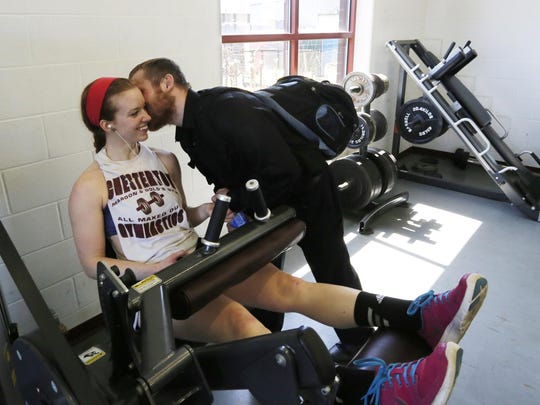 McCoy gives his girlfriend, Alyssa White, a kiss as she works out. When McCoy still wore an ankle monitor, falling asleep at his girlfriend's house might have been a parole violation.