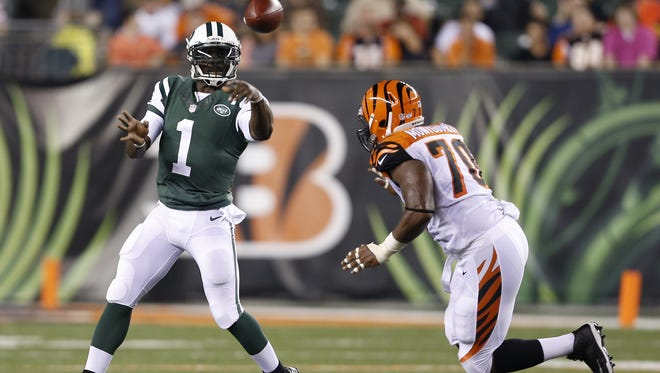 New York Jets quarterback Michael Vick (1) gets off a pass pressured by the Cincinnati Bengals defensive end Sam Montgomery (70) at Paul Brown Stadium.