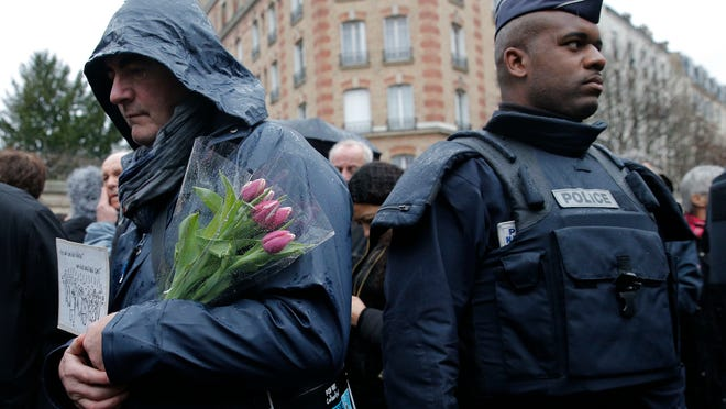 Christophe Ena/APA man holds flowers Thursday as he waits to enter at the Pere Lachaise cemetery during the funeral of cartoonist Bernard Verlhac, known as Tignous, in Paris.