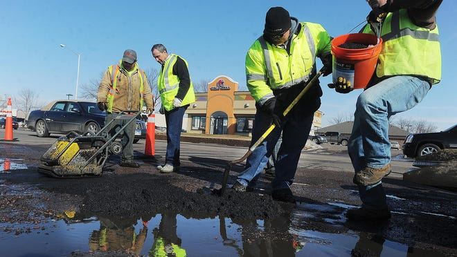 City of Sioux Falls employees along with city councilor Greg Jamison (second from left) work on filling the potholes along south Louise Avenue near the Empire Mall on Thursday, Feb. 18, 2016.