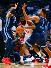 The Rockets' James Harden (13) tries to dribble through a double team of Grizzlies forward Kyle Anderson (1) and guard Dillon Brooks (24) during the first half Tuesday.