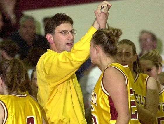 -Roosevelt girls basketball coach Fred Tibbetts high fives Renae Luecke as they celebrate the team's 101st straight win.