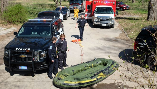 In this photo taken Monday, April 27, 2015, rescue vehicles block a Mason City street after two men were towed to safety from the Winnebago River. Police say the men's raft, pictured, became stuck near a dam south of 12th Street Northeast.