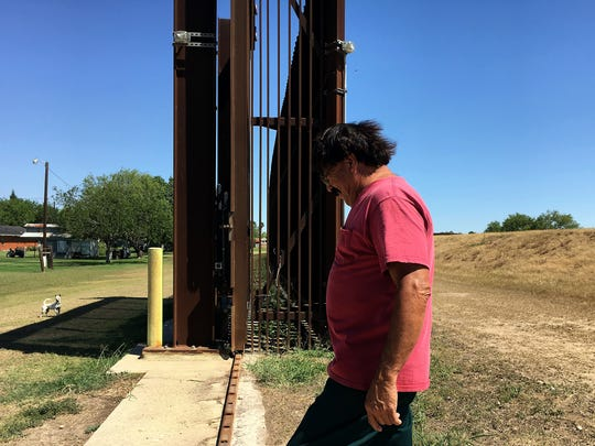 Jose Manuel Reyes walks against the border fence that is located in his backyard on Wednesday, May 25, 2017, at his home in Brownsville.