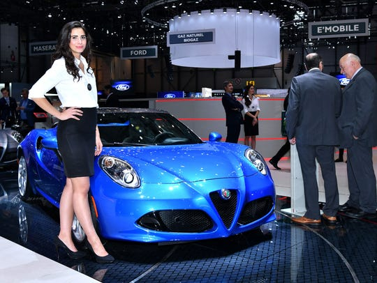 A hostess poses next to the new Alpha Romeo 4C Spider