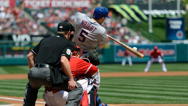 The Mets' David Wright hits an RBI single in the first inning against the Angels on Sunday. Wright would get ejected in the seventh inning for arguing balls and strikes.