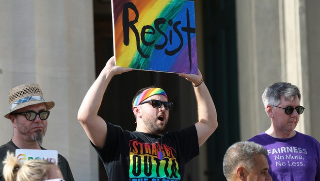 Christopher Heath held up a sign to protest the recent Supreme Court ruling in favor of a Colorado baker who declined to bake a cake for a same-sex couple.  The rally was held at Louisville's Metro Hall.June 4, 2018