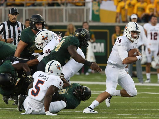 UTSA quarterback Dalton Sturm, right, slips past Baylor defensive end Xavier Jones, left, on a short run during the first half of an NCAA college football game, Saturday, Sept. 9, 2017, in Waco, Texas. (Michael Bancale/Waco Tribune Herald, via AP)