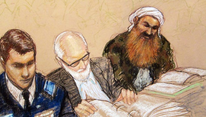 In a courtroom sketch, Khalid Sheikh Mohammed reviews court documents with his lawyers during the pretrial hearing of the death penalty case against five Sept. 11 attack suspects at the Guantanamo Bay U.S. Naval Base.