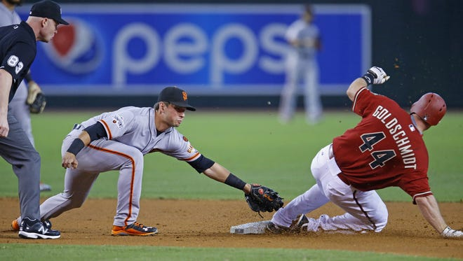 Arizona Diamondbacks' Paul Goldschmidt (44) slides safe on a double under the tag of San Francisco Giants second baseman Joe Panik (12) during the first inning of their MLB game Sunday, July 19, 2015 in Phoenix, Ariz.