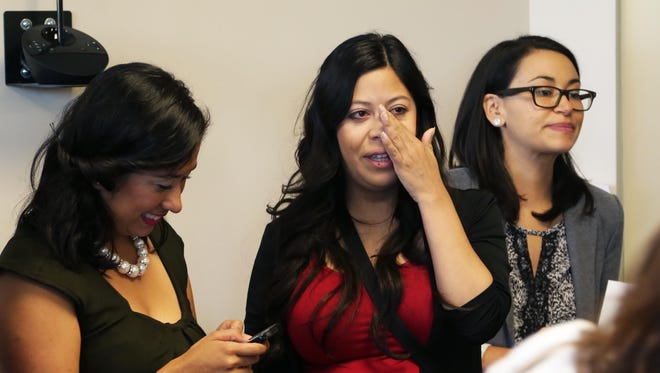 """""""Dreamer"""" Korina Uribe (center) reacts with tears after hearing the Arizona Board of Regents' decision after their meeting on Thursday, May 7, 2015."""