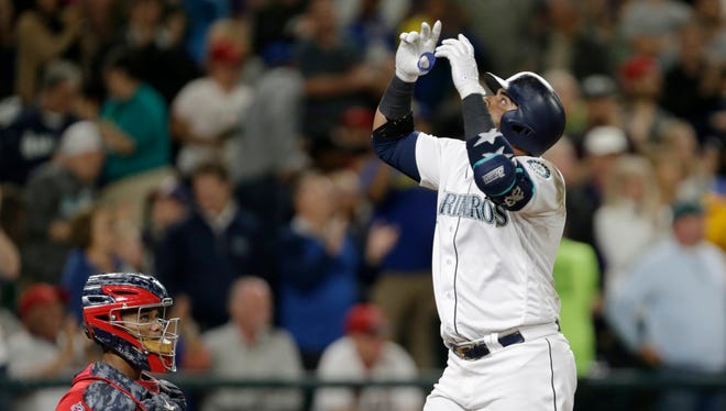 Seattle Mariners' Nelson Cruz points to the sky as he crosses home plate after hitting a three-run home run off Los Angeles Angels' Jesse Chavez during the fourth inning of Saturday's game.
