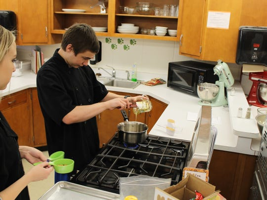 Plymouth High School culinary arts students prepare a crunchy popcorn snack for the Nourish Snack Attack program.