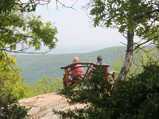 A couple enjoys the view from a bench on top of Bear Mountain.