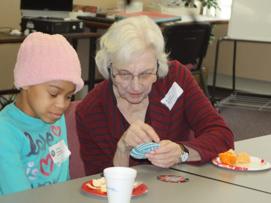 Next member Karen DiChera works on crafts with a student at Greenfield Elementary School.