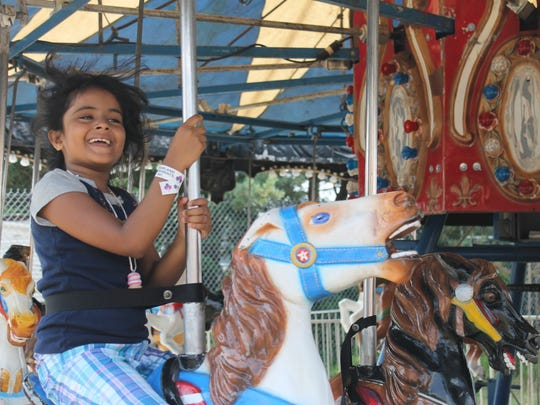 Neme Ciuze, 8, of Queens, New York, goes for a carousel ride at the Franklin County Field Days.