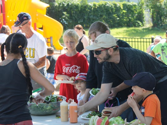 Diners load up on fresh salad and watermelon at the welcome back barbecue event.