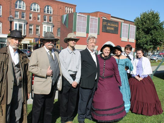 Re-enactors, including Andy Wooten and stage stage manager Kathleen Hoffman, center, pose in the St. Albans Raid facades in Taylor Park Friday morning.