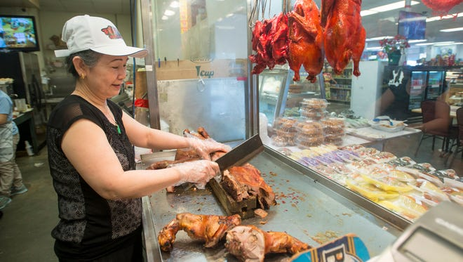 Minh Dang cuts pork in the Bien Dong Oriental Market in Brownsville on Friday, June 1, 2018.