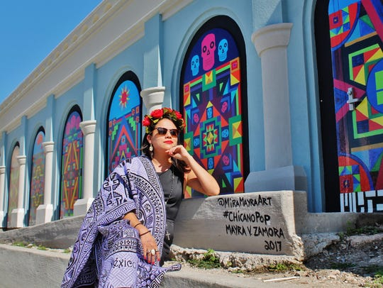 Mayra Zamora poses in front of her Chicano Pop mural