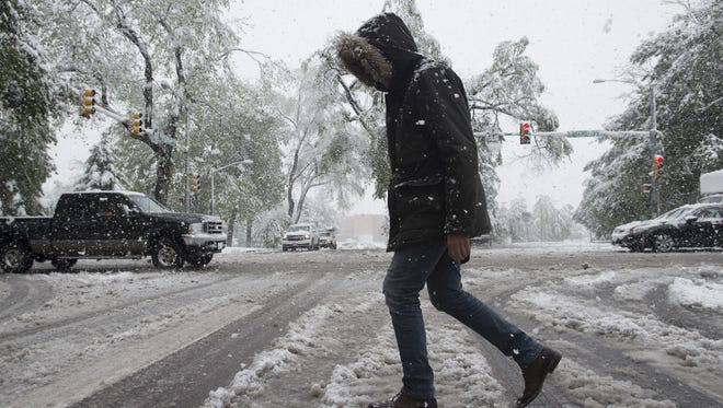 Mohammed Aymen navigates puddles of slush forming in the crosswalk at Howes Street and Laurel Street in this Coloradoan file photo. Fort Collins could see its first snow of the season Monday.