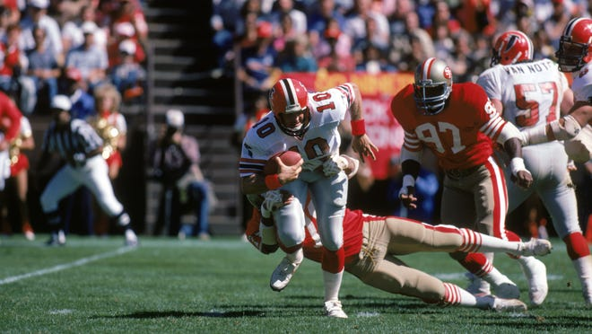 SAN FRANCISCO - SEPTEMBER 30:  Quarterback Steve Bartkowski #10 of the Atlanta Falcons tries to break a tackle as he scrambles for yards during a game against the San Francisco 49ers at Candlestick Park on September 30, 1984 in San Francisco, California.  The 49ers won 14-5.  (Photo by George Rose/Getty Images)
