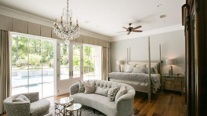 Master bedroom featuring custom-designed four poster bed in metallic hand-applied finish, seating area with custom love seat and swivel chairs, custom draperies that are motorized and remotely operated, antique crystal chandelier.