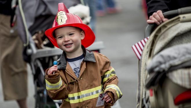 Owen Culloty, of St. Clair, eats a sucker while dressed as a fireman during a Safety Town event.