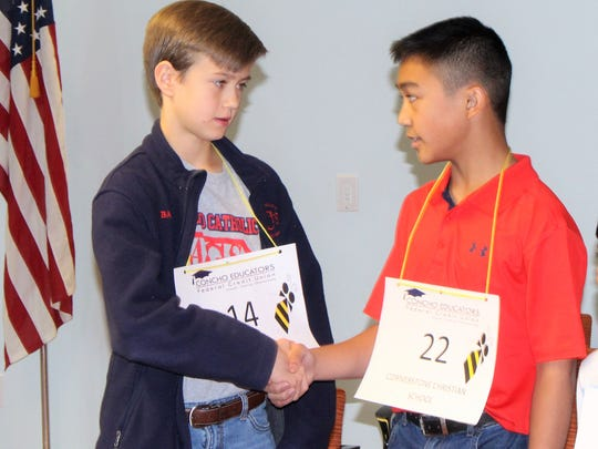 Davis Bailey, a 7th grader at Angelo Catholic School, shakes the hand of Kasey Torres, a 7th grader at Cornerstone Christian School, after Torres wins the 30th annual San Angelo Spelling Bee