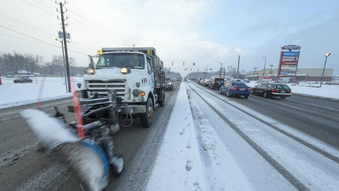 A Department of Public Works snowplow heads southbound on North Keystone Avenue, near Ruth Drive, on a snowy morning that brought about two inches of overnight and morning snow to the central Indiana area, Tuesday, Jan. 12, 2016. More light snow should fall before noon, and temperatures in the single digits are expected overnight.