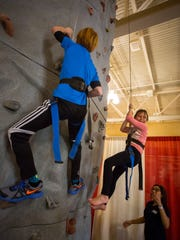 8-year-old Tessa Wedekind, center, smiles as she comes down an indoor climbing wall at the Mesilla Valley Outdoor Expo at the Las Cruces Convention Center on Saturday.