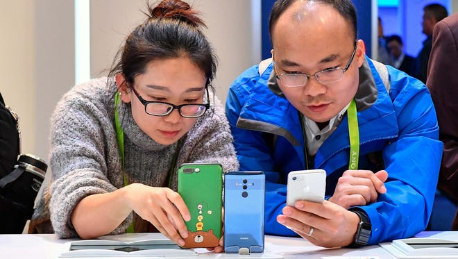 Weibin Chen, left, and Zhuo Li look over the Huawei Mate 10 Pro cellphone.
