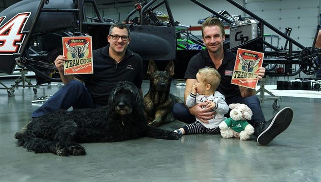 Pictured here is President of The Tony Stewart Foundation, Tony Stewart, his German Shepherd Max, the Goldendoodle is the Team One Cure Ambassador, Monty, Verizon IndyCar Series Driver, Jay Howard, and his one-year old son, Hudson.