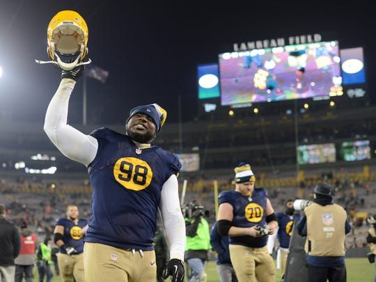 Green Bay Packers defensive tackle Letroy Guion (98) raises his helmet triumphantly as he leaves the field after the Packers defeated the Eagles.