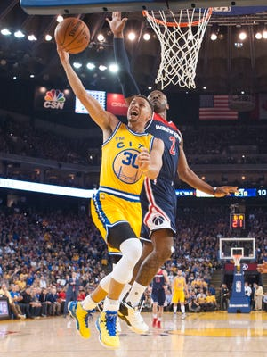Golden State Warriors guard Stephen Curry (30) drives to the basket past Washington Wizards guard John Wall (2) during the first quarter at Oracle Arena.