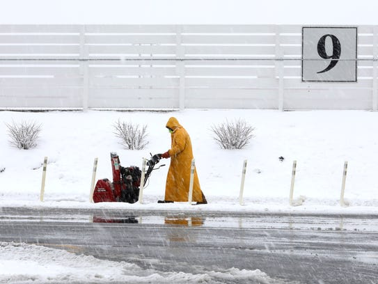 2:31 p.m. A worker clears the walking path at Empire