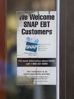 The lawsuit against the U.S. Department of Agriculture seeks the yearly amounts that taxpayers have paid grocers, gas stations and other businesses that participate in SNAP. A sign on the door of Apples and Oranges Fresh Market in Baltimore shows SNAP is accepted there.