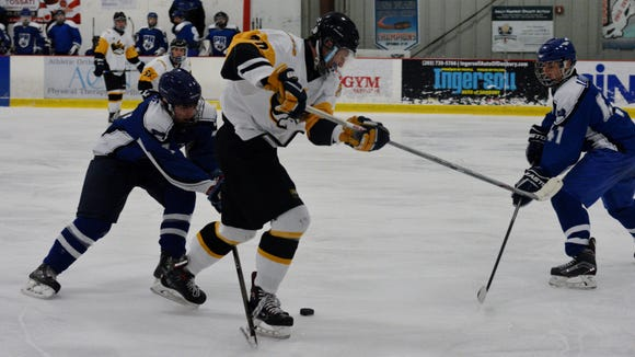 Brett Hanson (20) battles to retain control of the puck on Sunday during a 3-1 win over Pearl River at Brewster Ice Arena.