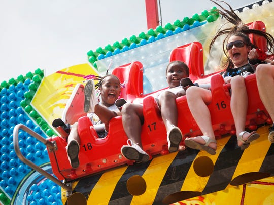 """Sisters Jakayla Cowan, 7, left, and Ajanae Littlejohn, 9, ride the X Factory ride at the North Carolina Mountain State Fair September 10, 2016. """"My stomach was dropping,"""" said Littlejohn."""