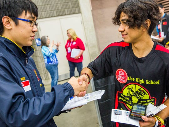 Immokalee High School Robotics Team senior Kristian Trevino, right, introduces himself to Wen Yuyi, 17, of the Anglo-Chinese School in Singapore during the Vex Robotics Competition World Championship in Louisville, Ky. on Friday, April 21, 2017. This is day two of three days of competition for the students.