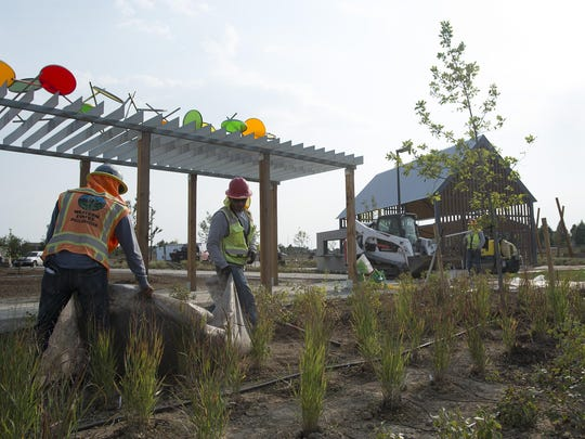 The final touches on landscaping are made at Twin Silo Park. The park, with a community garden and playground, is planned to open in late October.