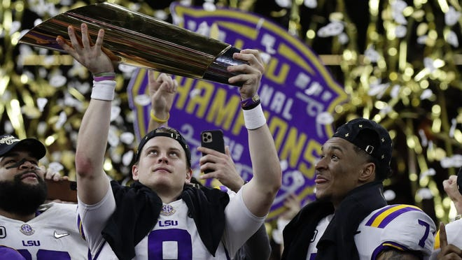 LSU quarterback Joe Burrow holds the trophy as safety Grant Delpit looks on after the national championship game against Clemson in January.
