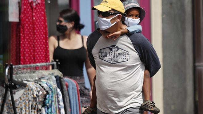 Shoppers walk by storefronts while wearing masks to protect against coronavirus, Saturday, July 25, 2020, in Bath, Maine.