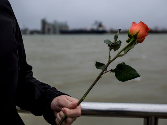 Participants throw flowers into the St. Clair River during a ceremonial flower toss in honor of National Crime Victims' Rights Week Thursday, April 6, 2017 at Kiefer Park in Port Huron.