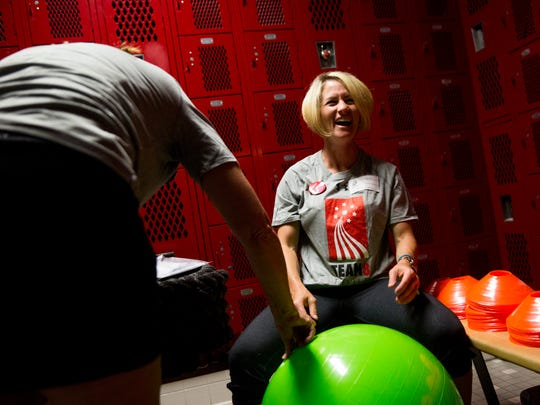 Beth Kilgore, a volunteer and employee with UnitedHealthcare, laughs after an exercise ball gets away from her while filling it with air as volunteers work to fill a new girls fitness training room at Immokalee High School on Tuesday, May 23, 2017, in Immokalee, Fla.